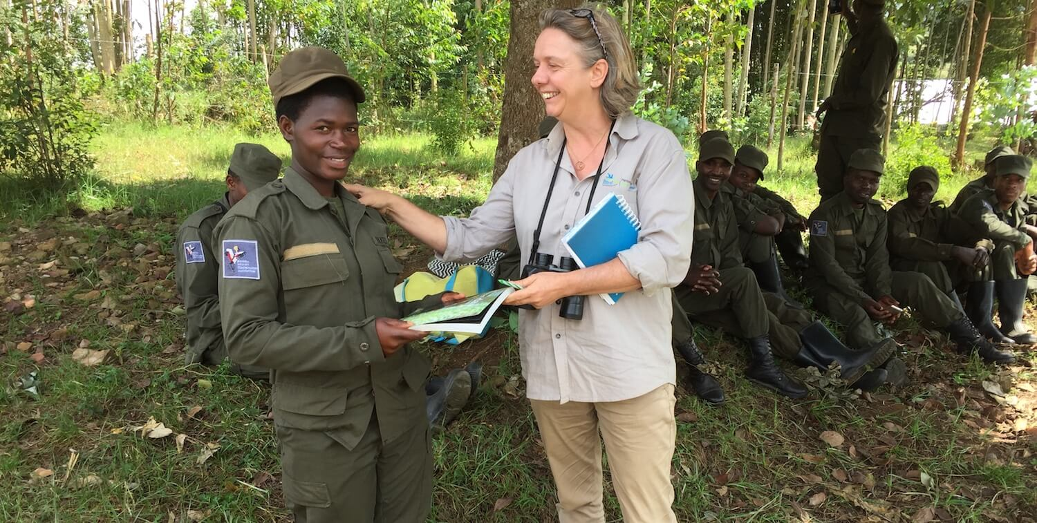 Woman with hand on shoulder of female ranger, both smiling.