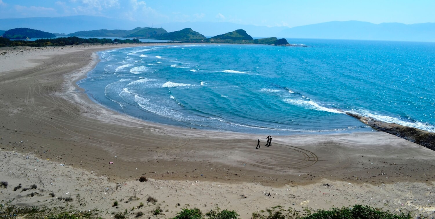 High-up view of a beach and water, three people walking along the sand.