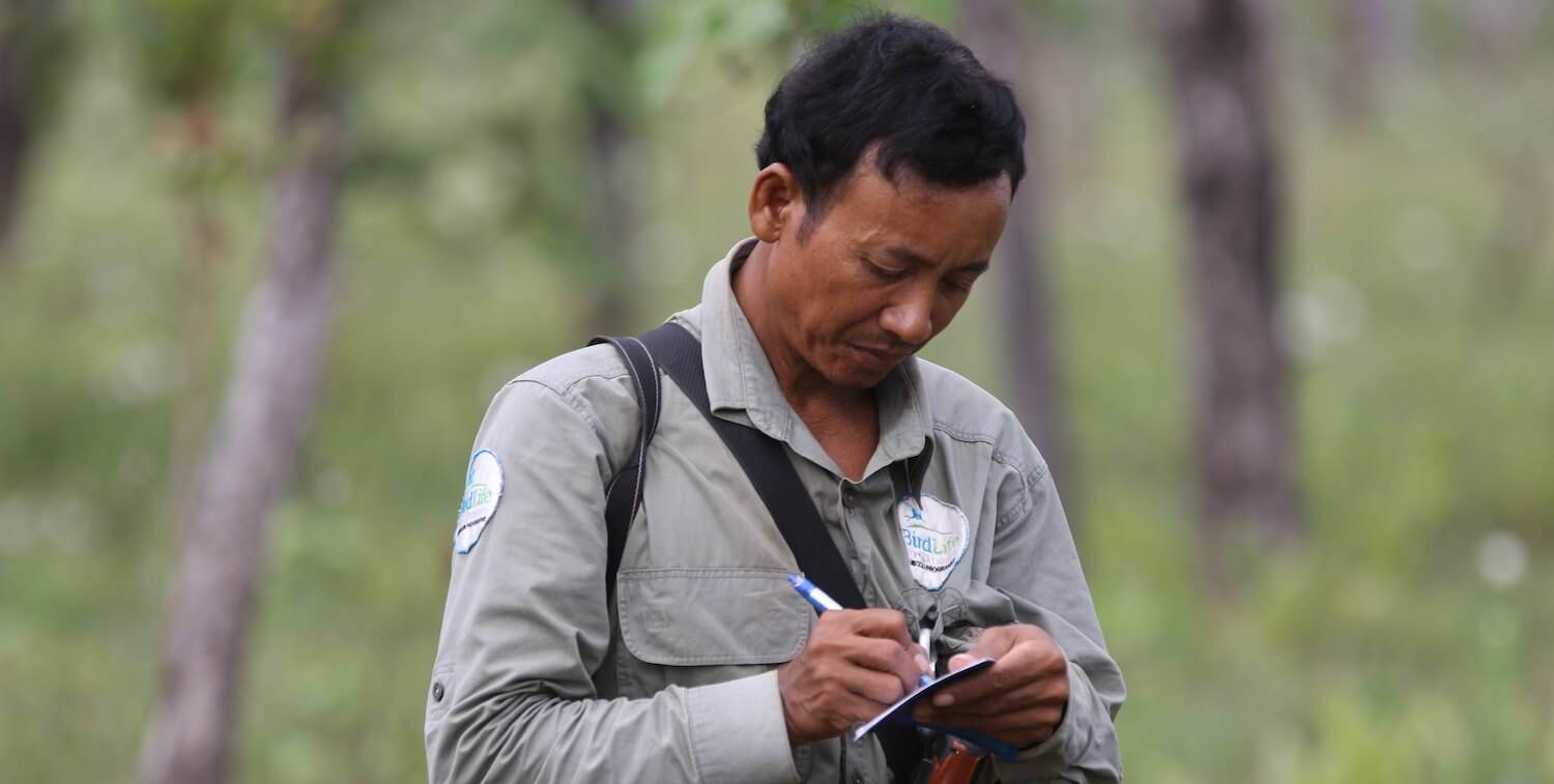Close-up of man outside with BirdLife patch writing in small notebook.