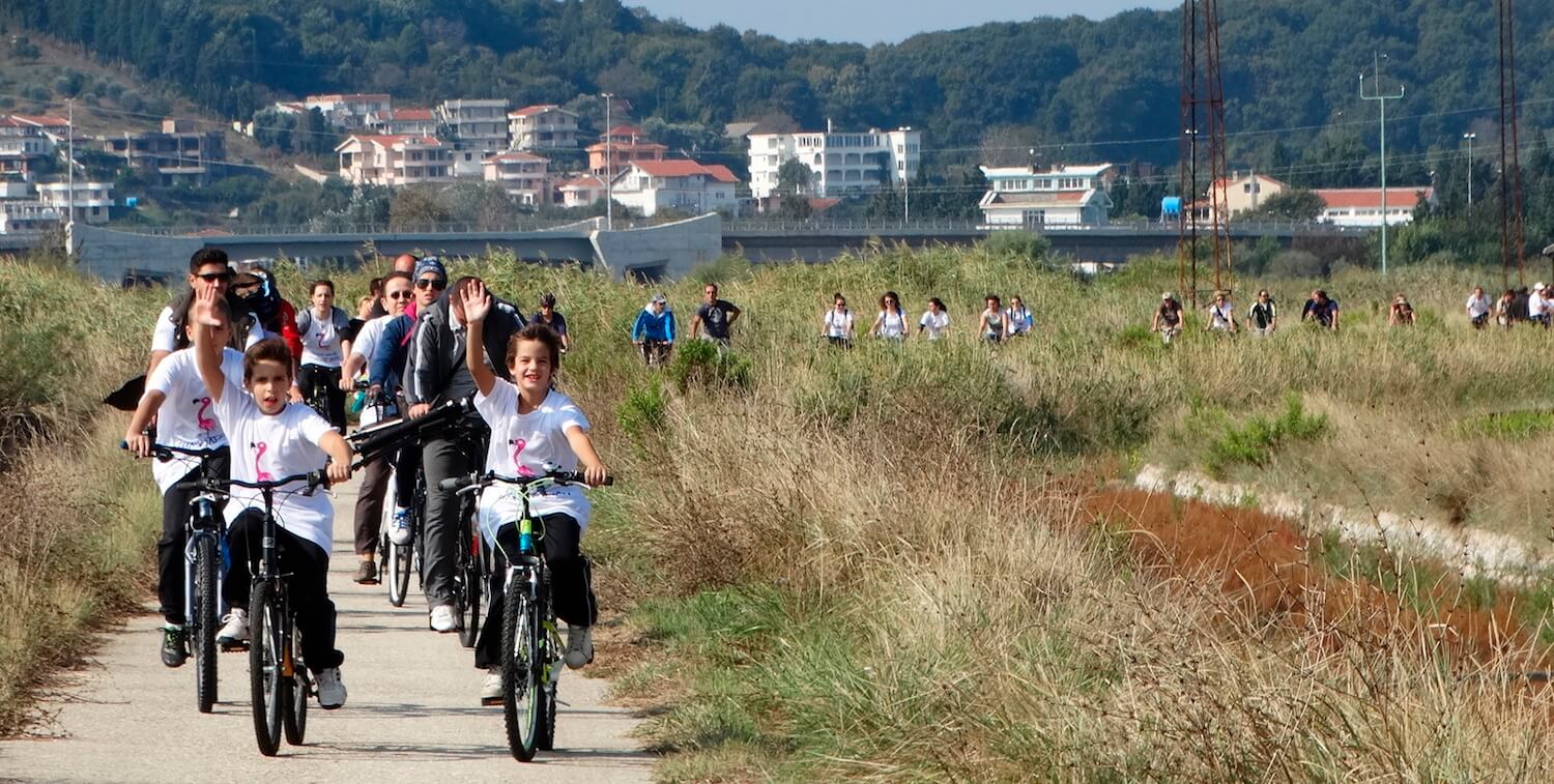 Group of children riding bikes down path, children in front smiling and waiving to camera.