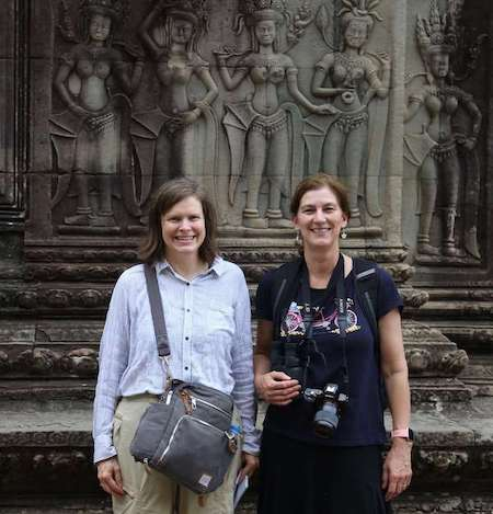 Two women standing outside of monument with representations of people carved into it.