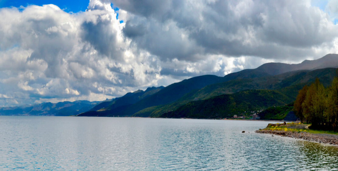 Vista of water with lush mountains in background, clouds and bright blue sky.