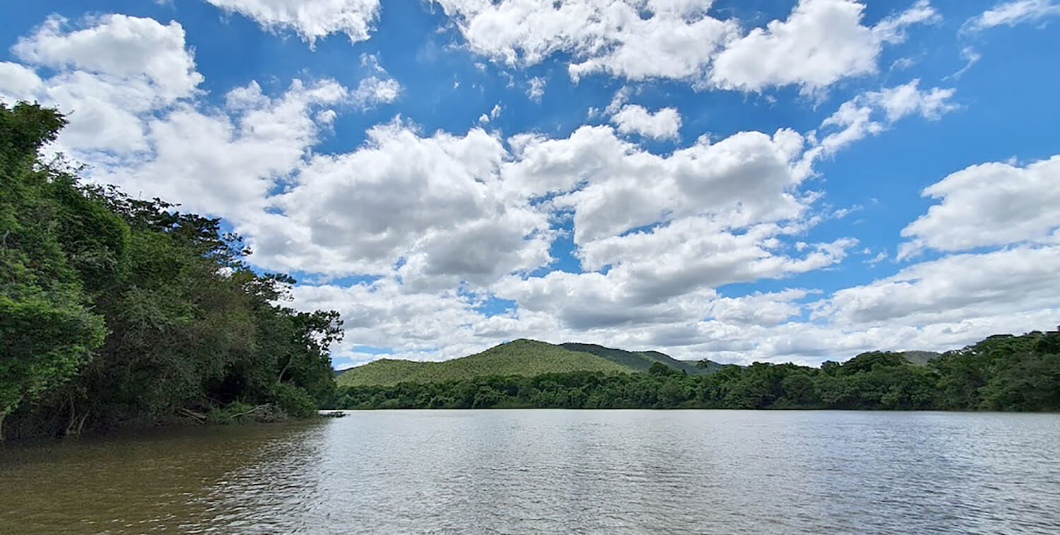 River vista, surrounded by green on three sides, blue sky with puffy, white clouds above.
