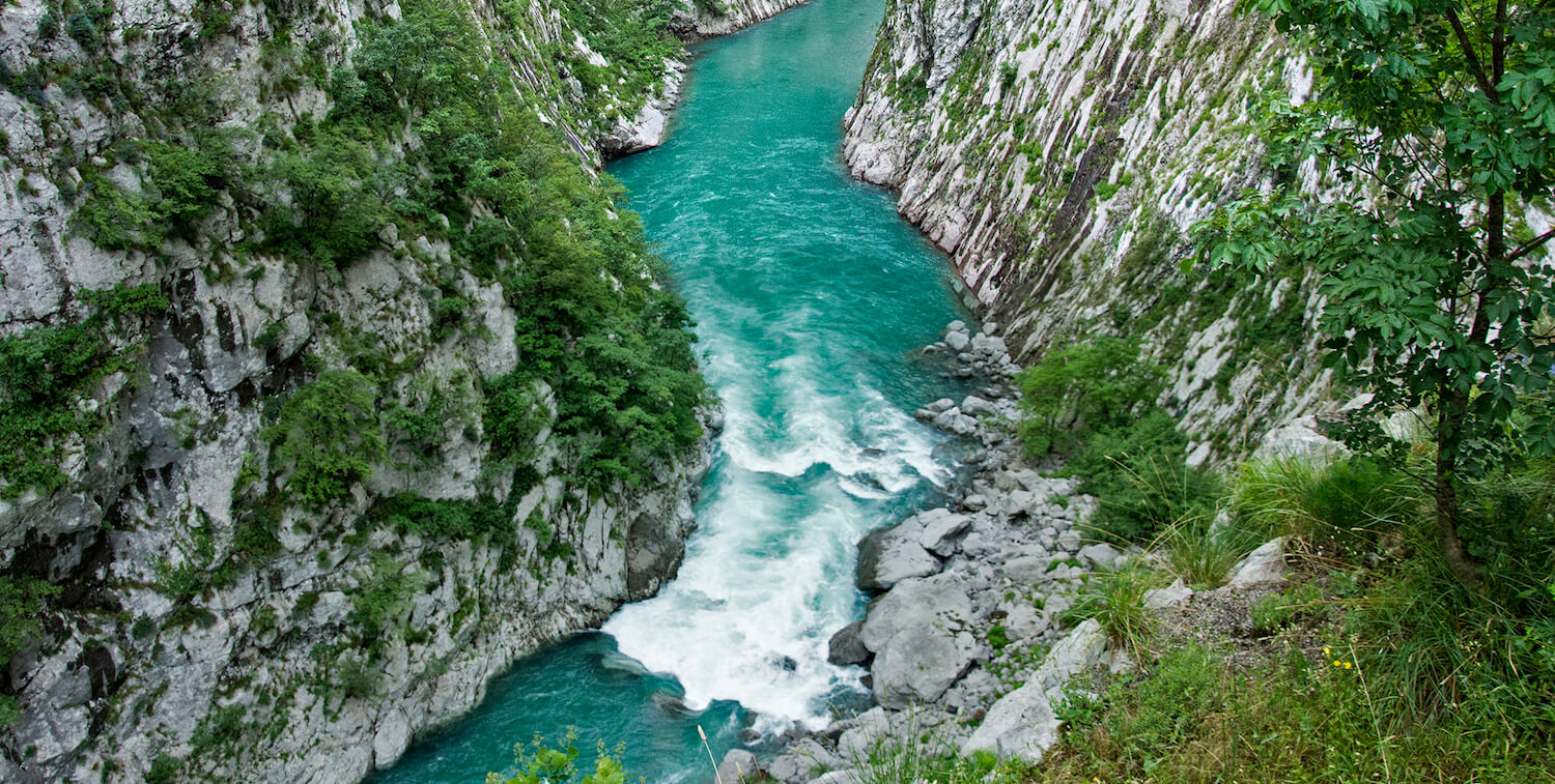 Turquoise-colored river running through high mountains with exposed rock.