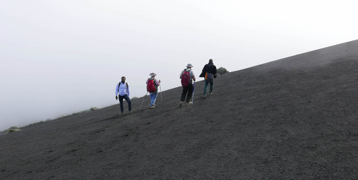 Four people climb up steep, black slope.