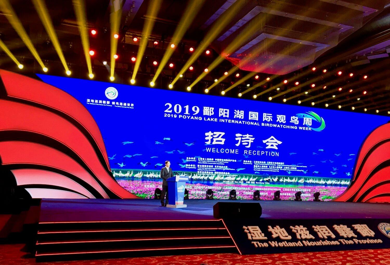 Man at podium on stage, digital sign stating 2019 Poyang Lake Birdwatching Week.