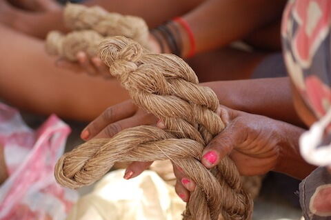 Close up of brown thread held by a woman's hands