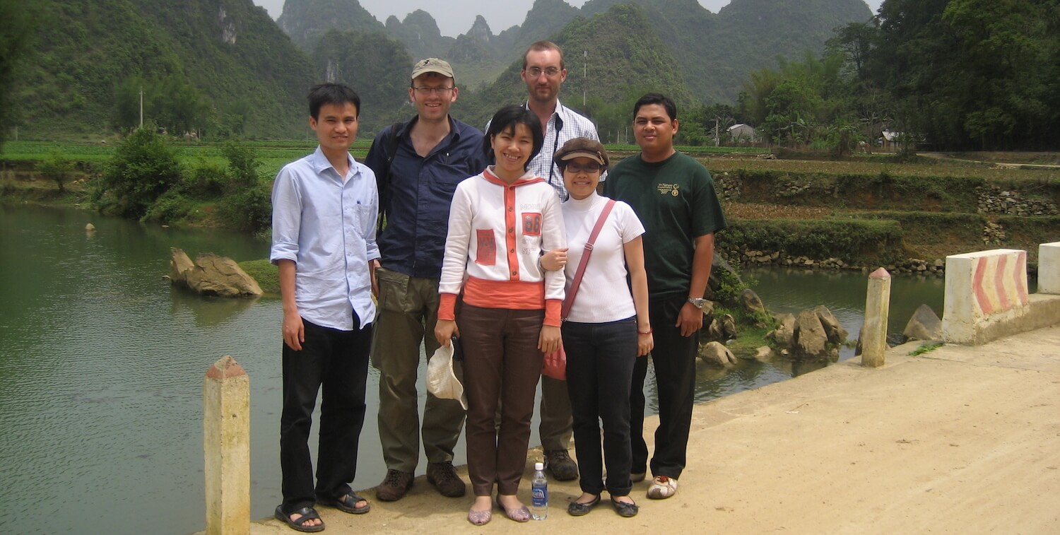 Group of people standing, smiling at camera.