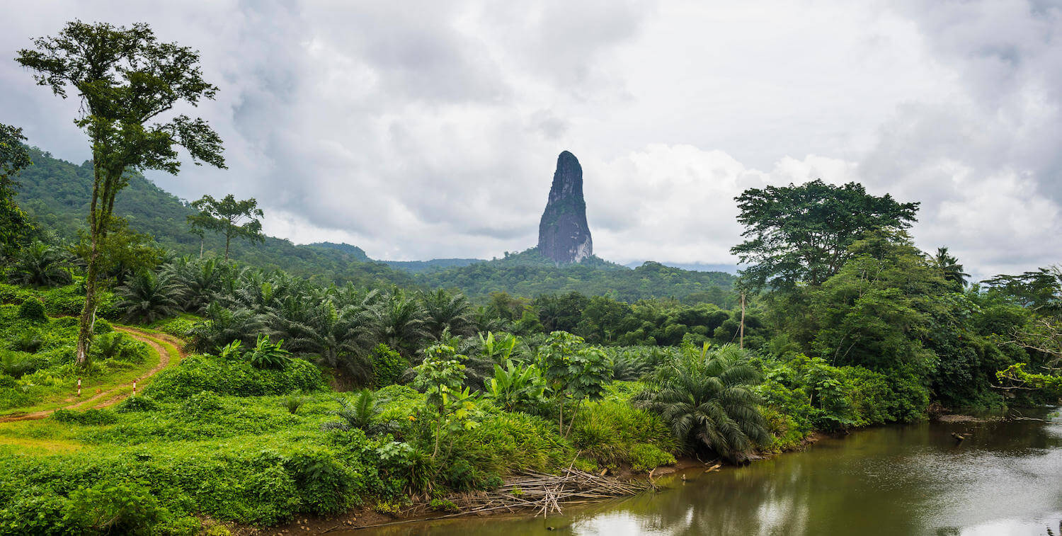 Lush green scenery, brown river in foreground and large, pointy monolith in background.