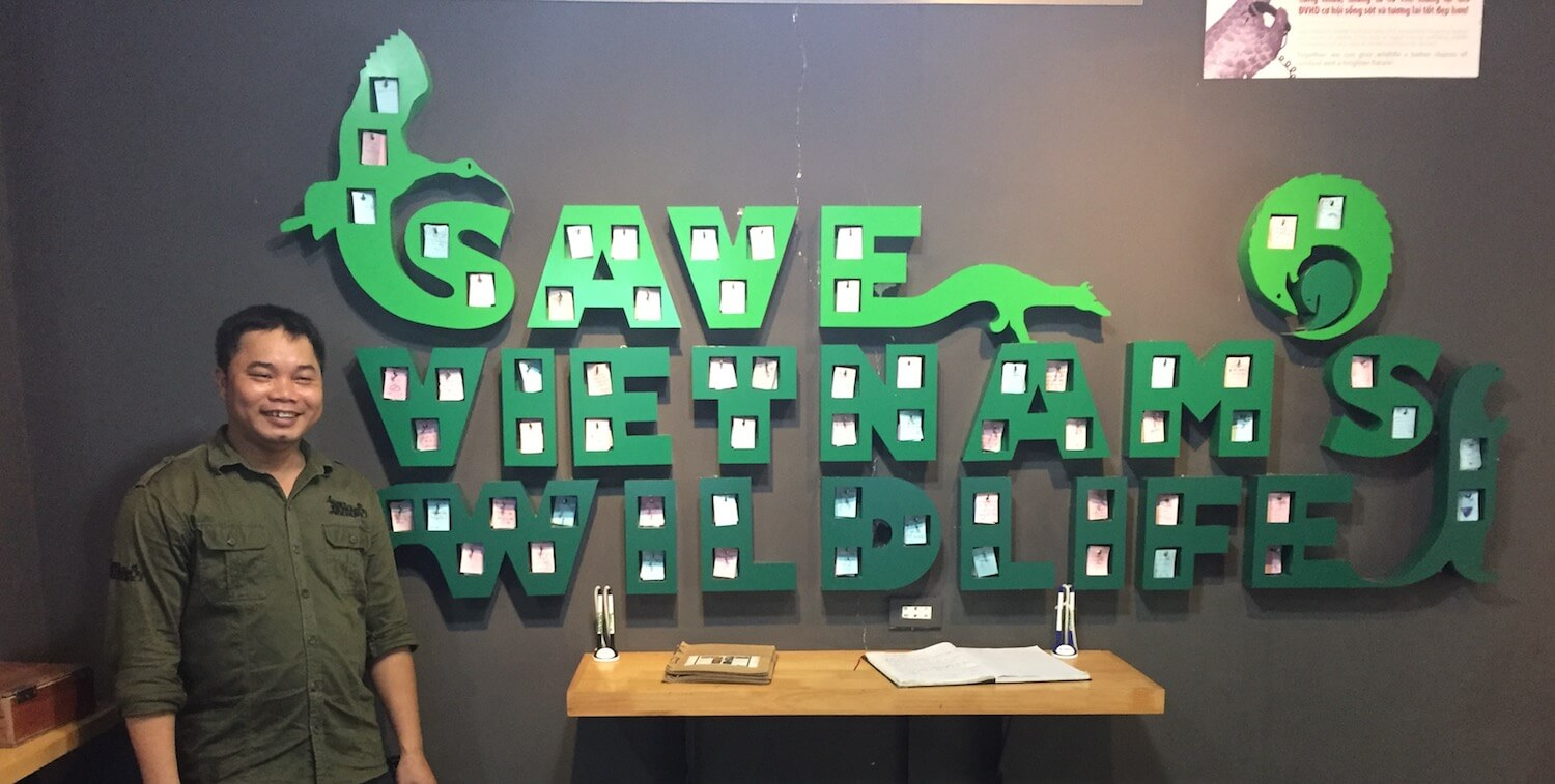 """Man standing next to large, green indoor wall sign that reads """"Save Vietnam's Wildlife."""""""