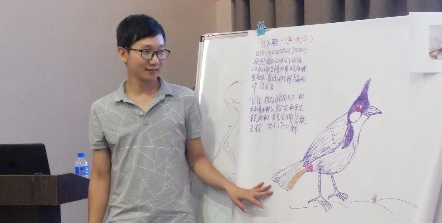 Young man looking at poster with bird drawing and Chinese writing.