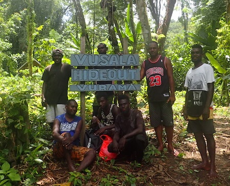 7 men standing/sitting around sign reading Vusala Hideout Vurama.