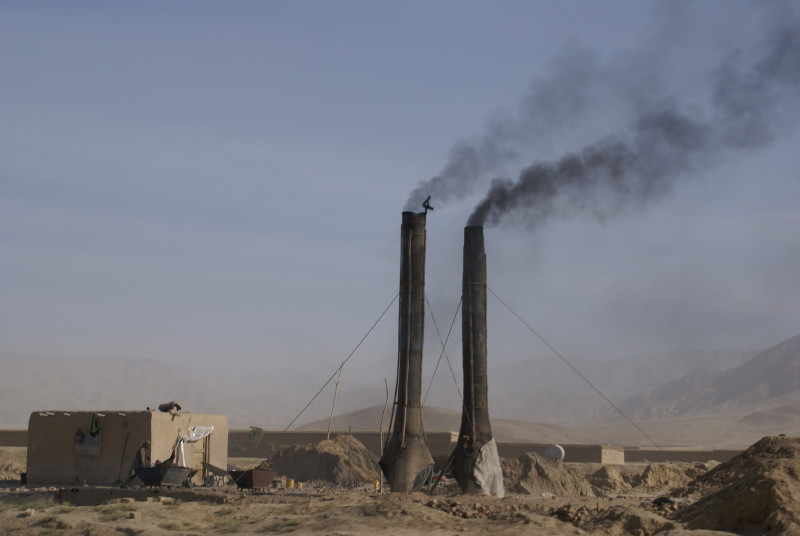 Two small smokestacks next to small building, amid barren landscape.