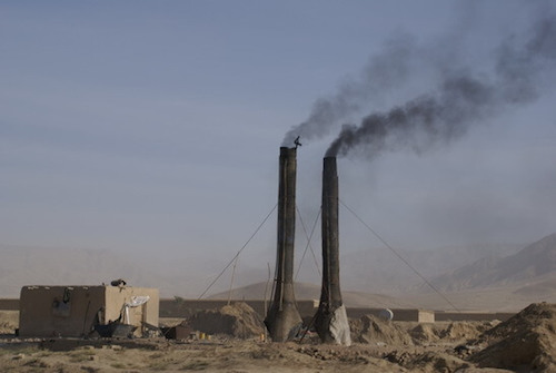 Two smokestacks near small building amidst barren landscape.