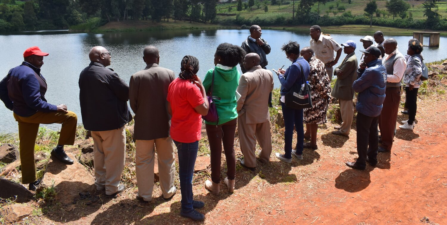 About 15 people standing in front of body of water, greenery in background.