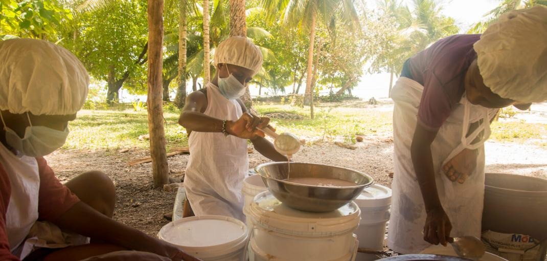 Three women with hairnets and facemasks working with bins of coconut oil.