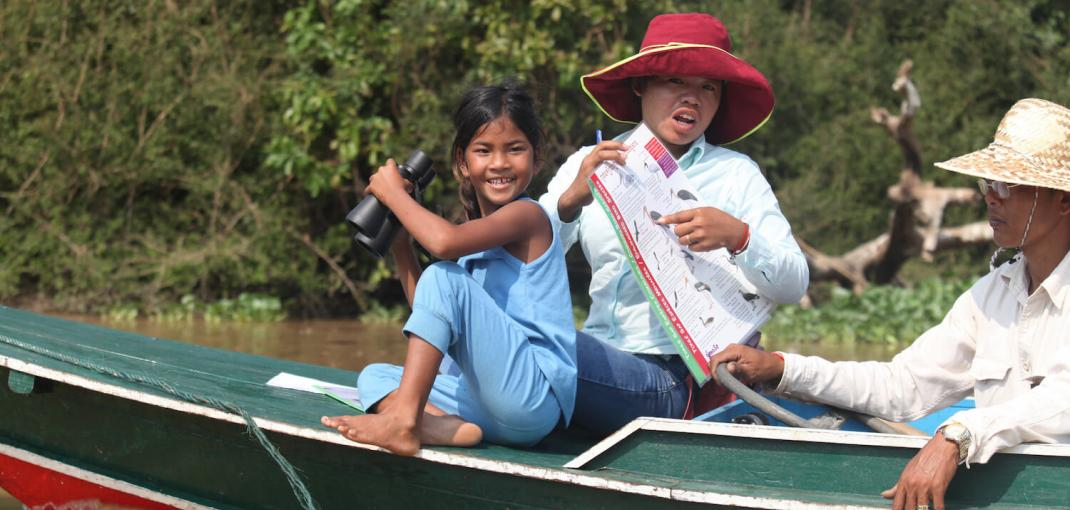 A young girl, a woman and a man ride a small boat on a river in a forested area.