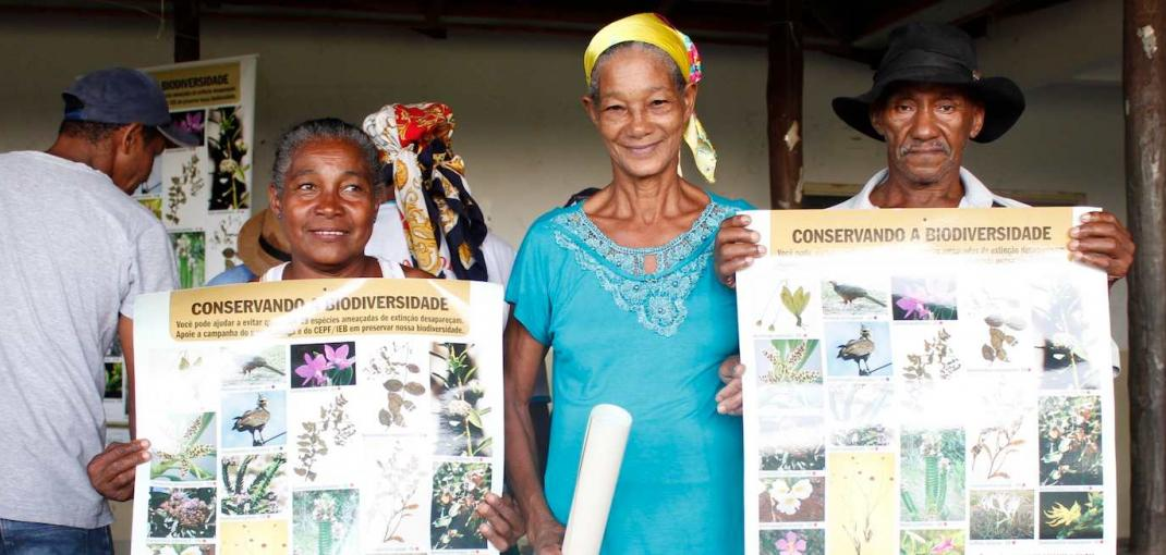 Two women and a man, all members of a Kalunga community in Brazil, hold up environmental education posters.