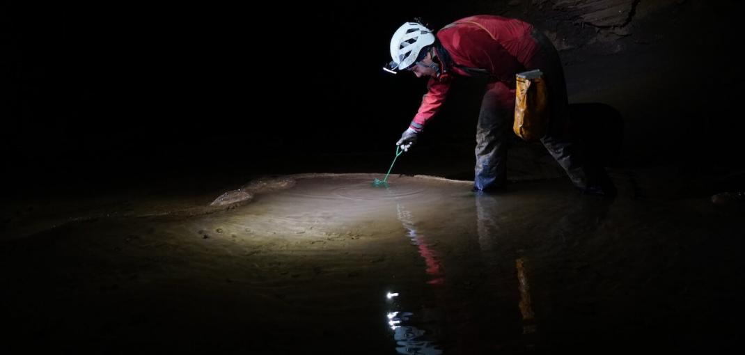 Person in cave taking water sample.