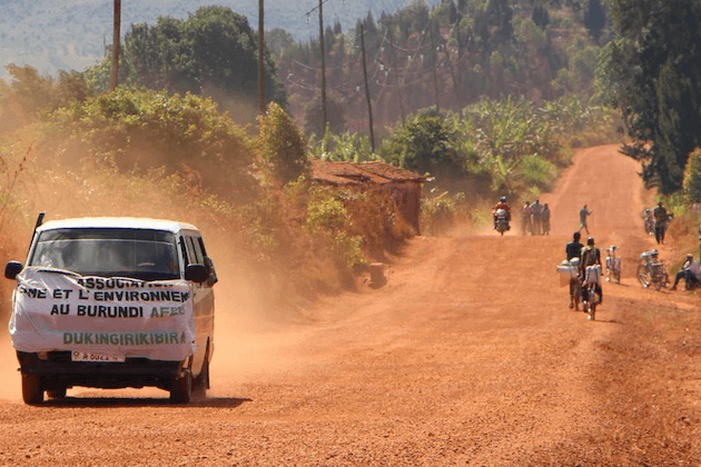 Van and a few people on a red dirt road.