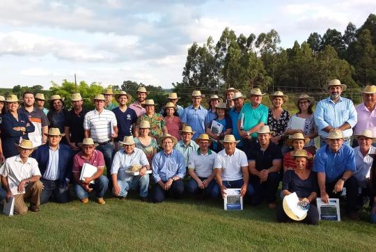 40 people wearing straw hats posing for a group photo outside.