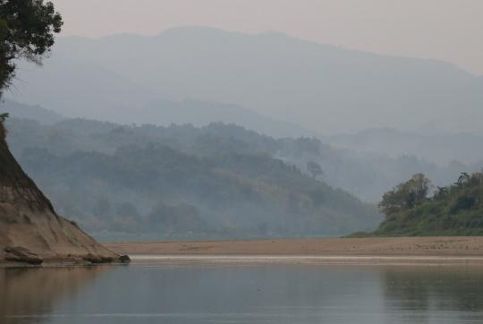 Vista, water in foreground, misty hills in background.