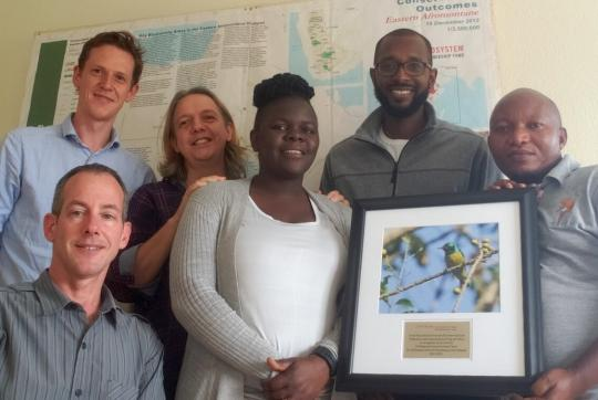 6 people indoors, smiling at camera. one person holds plaque with bird photo on it.