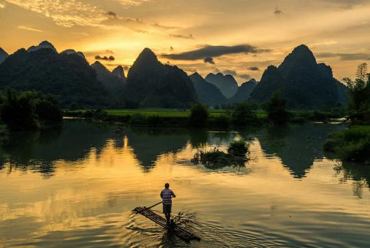 Man standing on thin raft made of logs, paddling across calm water as sun sets. Water is surrounding by high, pointed hills.