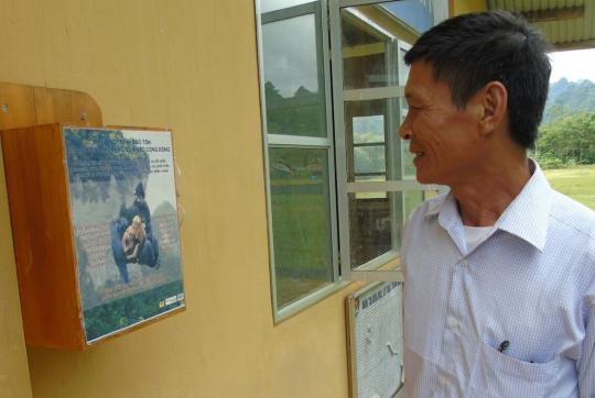 Man looking at box on wall with writing and photo of François' langur.