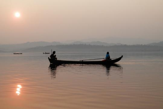 Two people on either end of canoe during sunset.
