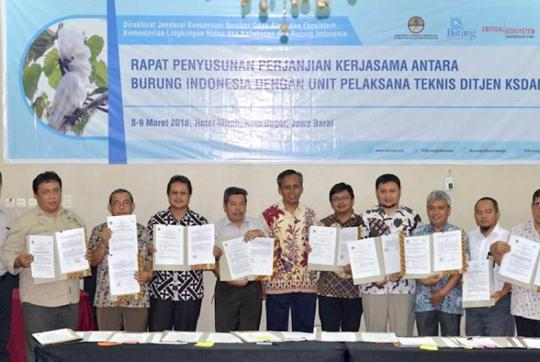 Group of 13 men smiling at camera, standing beneath sign written in Indonesian, many holding the signed MOUs.
