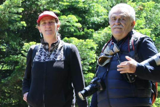 Nina and man looking at camera, trees behind them