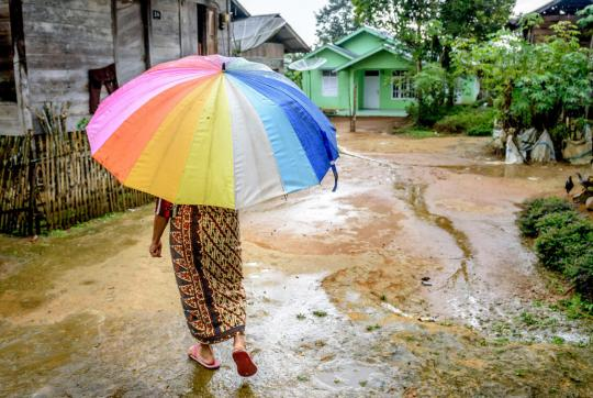 Woman with her back to camera holds a large, bright umbrella. She is walking on a dirt road, a few houses on either side.