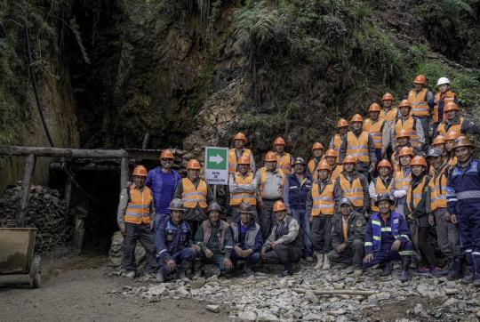 Group of about 25 miners, most wearing orange vests and hard hats, stand outside a mine.