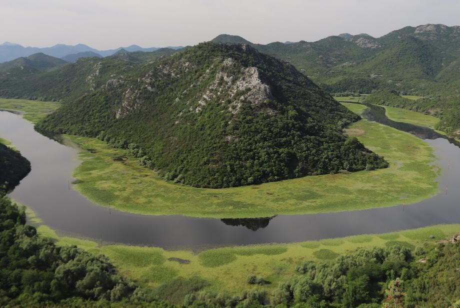 Lake circling around small mountain.