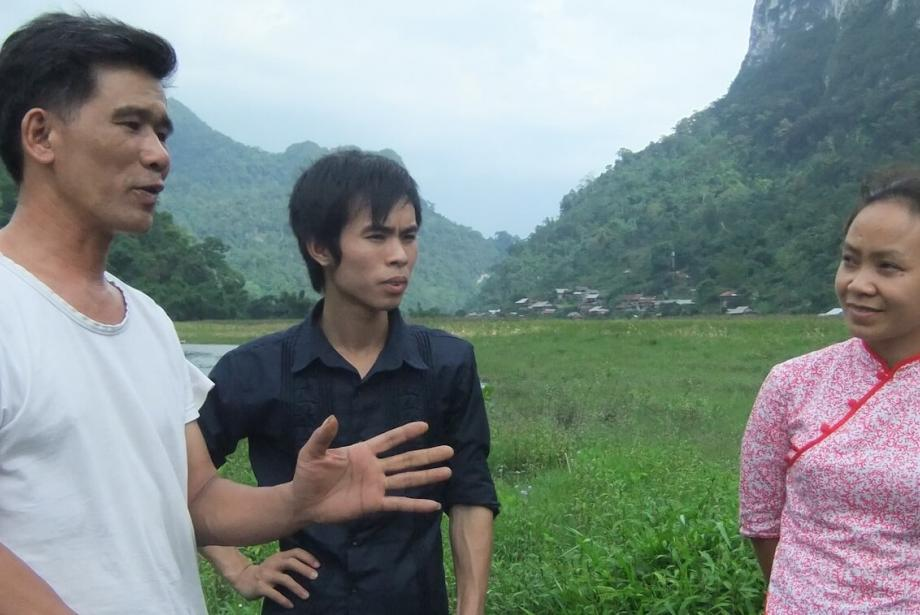 Two men and one woman having a discussion in the foreground, lush landscape in the background.