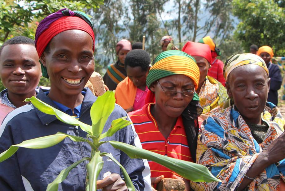 Community members in bright clothing. Woman in front is smiling and holding plant.