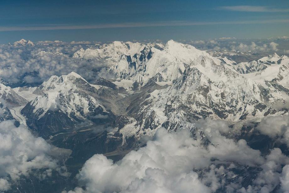 Aerial view of snowy mountains with smattering of clouds.