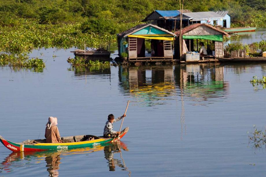 Brightly colored canoe on lake with two people, headed toward several floating buildings.
