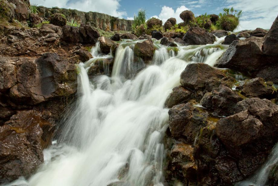 Waterfall against brown rocks.