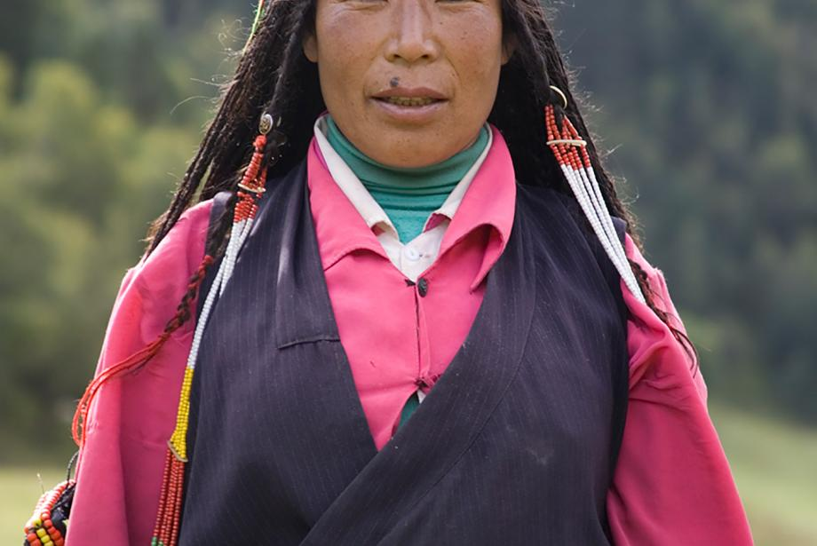 Portrait of woman standing outside in traditional dress.