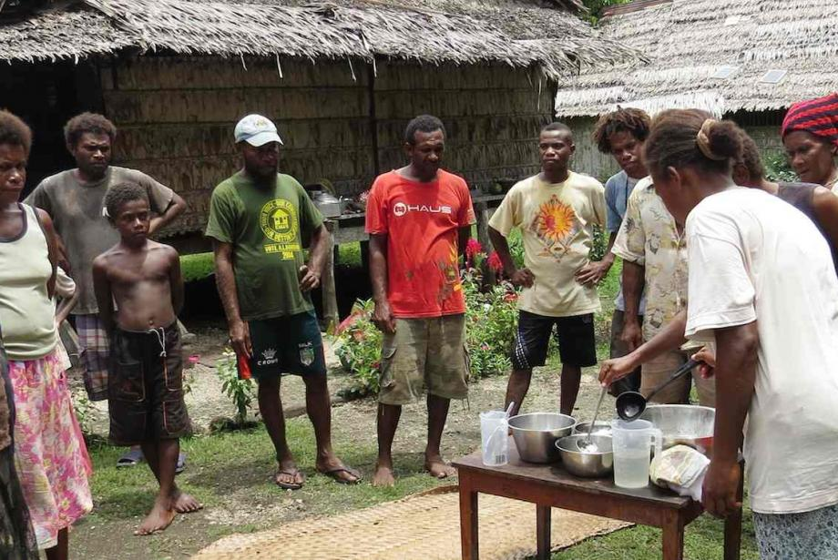 A group of men and women encircle a woman at a small table demonstrate coconut oil pressing.