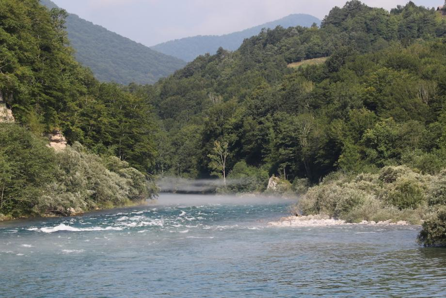 River, tree-covered hills on either side.