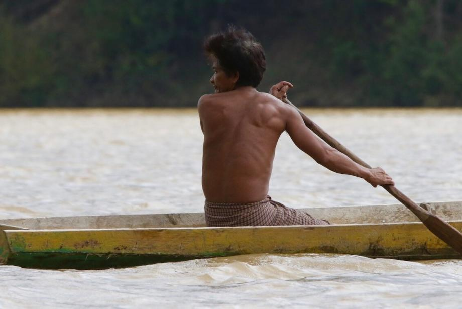 Man paddling wooden canoe, looks behind him.