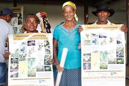 Two women and one man standing, smiling at camera. Two hold up matching posters with pictures of biodiversity.