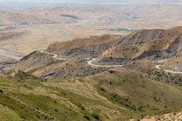 Brown mountainous landscape, road snaking along.