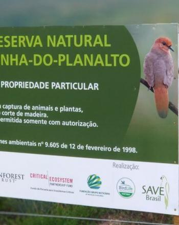 """Sign for """"Reserva Natural Rolinha-Do-Planalto with image of  blue-eyed ground-dove and list of funders, including CEPF, at the bottom."""