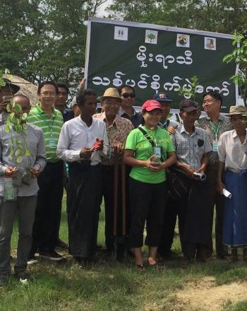 Group of about 20 people smiling, each holding a tree sapling.
