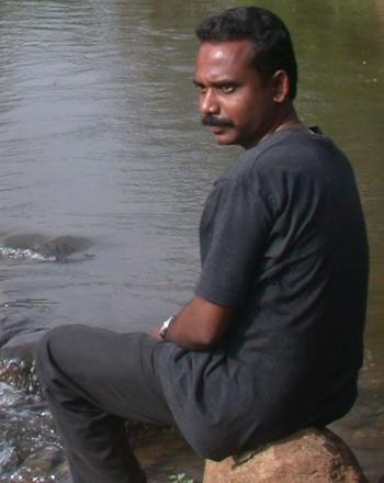 Man looking over shoulder, sitting by moving water.