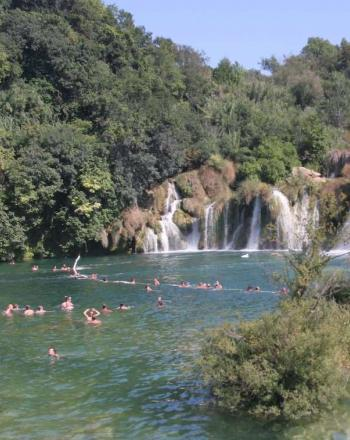 People swimming in emerald green water, series of waterfalls in the background.
